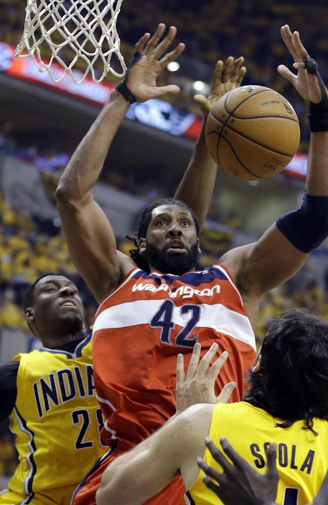 Indiana Pacers center Ian Mahinmi, left, blocks the shot of Washington Wizards forward Nene Hilario during the second quarter of game 1 of the Eastern Conference semifinal NBA basketball playoff series in Indianapolis, Monday, May 5, 2014