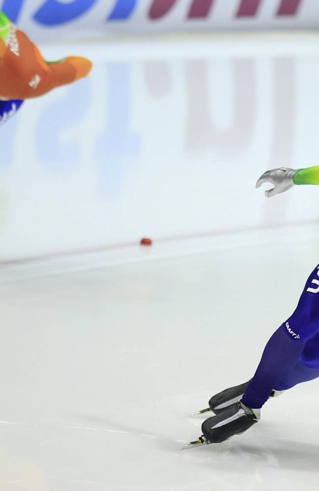 Ronald Mulder of the Netherlands, right, races his brother Michel, left, during the first heat of the men's 500-meter speedskating race during the World Cup final at Thialf skating arena, Saturday, March 15, 2014, in Heerenveen, northern Netherlands