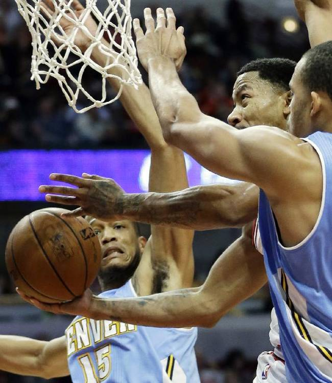 Chicago Bulls guard Derrick Rose, center, drives to the basket between Denver Nuggets forward Anthony Randolph, left, and center JaVale McGee during the second half of an NBA preseason basketball game in Chicago on Friday, Oct. 25, 2013. The Bulls won 94-89