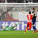 Olympiakos' Alejandro Dominguez, scores as Manchester United goalkeeper David de Gea, left, tries to stop the ball, during their Champions League, round of 16, first leg soccer match, at Georgios Karaiskakis stadium, in Piraeus port, near Athens, on Tuesd