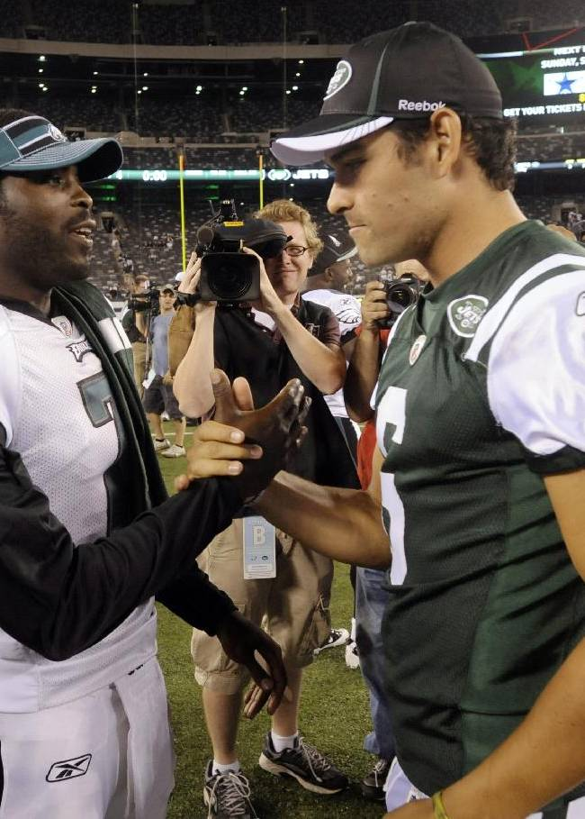 In this Sept. 1, 2011, file photo, Philadelphia Eagles' Michael Vick, left, greets New York Jets' Mark Sanchez after a preseason NFL football game in East Rutherford, N.J. The  Jets signed Vick and released Sanchez on Friday, March 21, 2014. Vick was a free agent after spending the last five seasons with the Phialdelphia Eagles