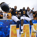 West Virginia's Shaquille Riddick (4) and K.J. Dillon (9) celebrate their win with fans following an NCAA college football game in Morgantown, W.Va., Saturday, Oct. 18, 2014. West Virginia won 41-27. (AP Photo/Chris Jackson)