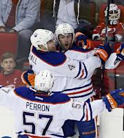 Edmonton Oilers' Justin Schultz (19) celebrates with teammates Taylor Hall (4) and David Perron (57) after Schultz's goal during the third period of an NHL hockey game in Raleigh, N.C., Sunday, March 16, 2014. Oilers won 2-1. (AP Photo/Karl B DeBlaker)
