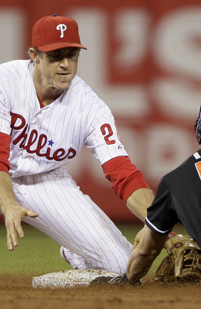 Miami Marlins' Ed Lucas, right, is tagged out by Philadelphia Phillies' Chase Utley while trying to steal second during the third inning of a baseball game on Wednesday, Sept. 18, 2013, in Philadelphia