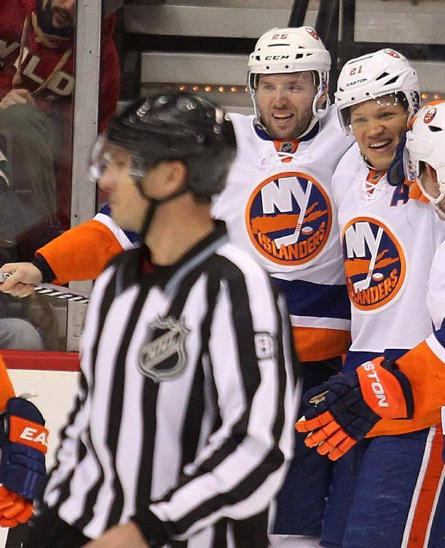 New York Islanders forward Kyle Okposo, second from right, is congratulated by the teammates after scoring a goal against the Minnesota Wild during the third period of their NHL hockey game won by the Islanders 5-4, Sunday, Dec. 29, 2013, in St. Paul, Minn