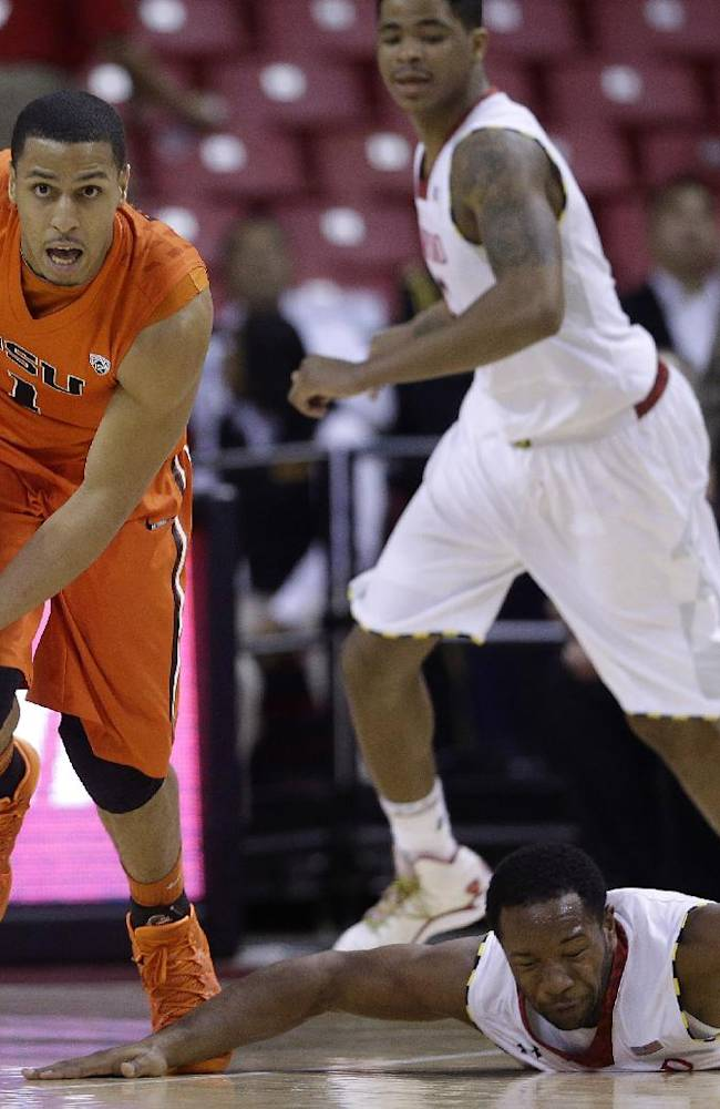 Oregon State's Victor Robbins, left, drives past Maryland guards Dez Wells, bottom right, and Nick Faust during the second half of an NCAA college basketball game in College Park, Md., Sunday, Nov. 17, 2013. Oregon State won 90-83