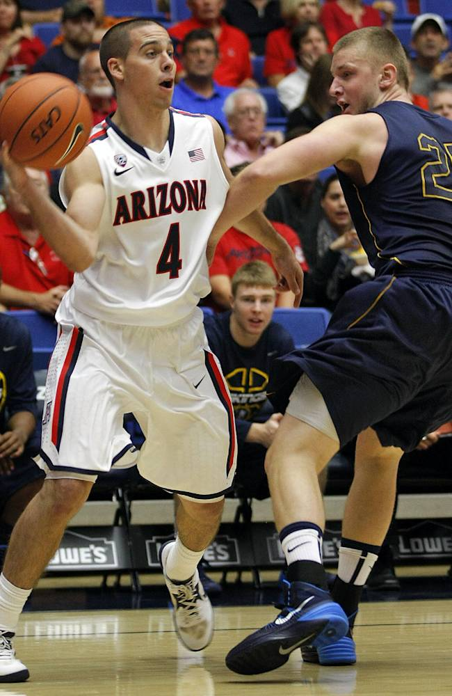 Arizona's T.J. McConnell (4) passes the ball around the defense of Austana's Yuriy Malashenko (25) in the first half of an college exhibition basketball game, Monday, Oct. 28, 2013 in Tucson, Ariz