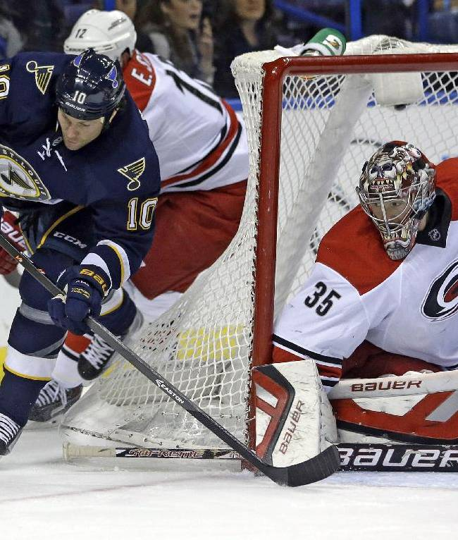 St. Louis Blues' Brenden Morrow, left, reaches for a loose puck as Carolina Hurricanes goalie Justin Peters, right, watches during the second period of an NHL hockey game Saturday, Nov. 16, 2013, in St. Louis
