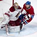 Montreal Canadiens' Lars Eller runs into Phoenix Coyotes goalie Mike Smith during the first period of an NHL hockey game Tuesday, Dec. 17, 2013, in Montreal. (AP Photo/The Canadian Press, Paul Chiasson)
