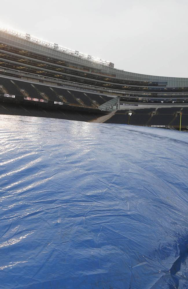 A member of the grounds crew stand by the tarp as air is blow onto the field before an NFL football game between the Chicago Bears and Minnesota Vikings, Sunday, Sept. 15, 2013, in Chicago