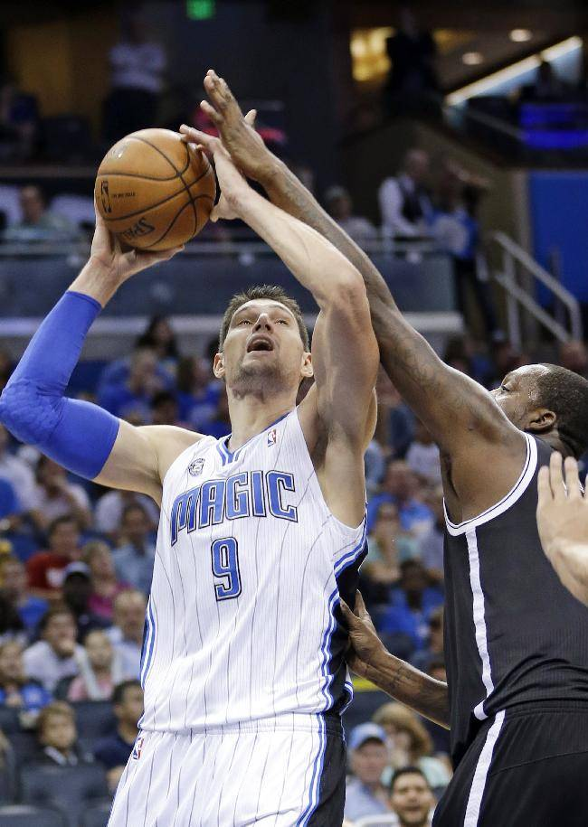 Orlando Magic's Nikola Vucevic (9), of Montenegro, makes a shot over the arm of Brooklyn Nets' Andray Blatche, right, during the second half of an NBA basketball game in Orlando, Fla., Sunday, Nov. 3, 2013. Orlando Magic won 107-86