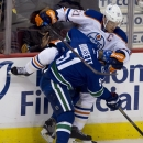 Vancouver Canucks right wing Derek Dorsett (51) goes into the boards with Edmonton Oilers defenceman Andrew Ference (21) during the third period of NHL action in Vancouver, British Columbia Saturday, Oct. 11, 2014 The Associated Press