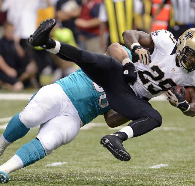 New Orleans Saints running back Khiry Robinson (29) is thrown to the ground by Miami Dolphins defensive end Paul Soliai in the first half of an NFL football game in New Orleans, Monday, Sept. 30, 2013