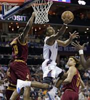 Charlotte Bobcats' Ramon Sessions, center, drives past Cleveland Cavaliers' Anderson Varejao, right, and Tristan Thompson, left, during the first half of an NBA basketball game in Charlotte, N.C., Friday, Nov. 1, 2013. (AP Photo/Chuck Burton)