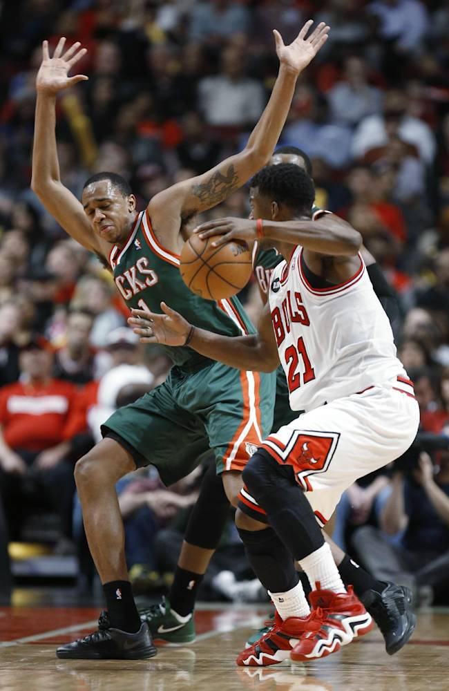 Milwaukee Bucks forward John Henson, left, defends Chicago Bulls guard Jimmy Butler during the second half of an NBA basketball game in Chicago, Friday, April 4, 2014. The Bulls won 102-90