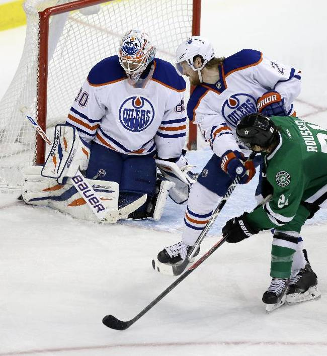 Dallas Stars' Antoine Roussel (21) of France and Edmonton Oilers' Jeff Petry (2) watch as Oilers goalie Ilya Bryzgalov (80) deflects a shot in the third period of an NHL Hockey game, Tuesday, Jan. 14, 2014, in Dallas