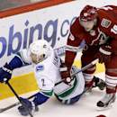 Phoenix Coyotes' Shane Doan (19) sends Vancouver Canucks' Dan Hamhuis (2) to the ice during the second period of an NHL hockey game on Tuesday, March 4, 2014, in Glendale, Ariz The Associated Press
