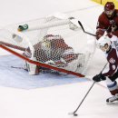 As Colorado Avalanche's Matt Duchene (9) moves to the net to shoot the puck, Arizona Coyotes' Mike Smith, left, has the goal fall over on him as Coyotes' Keith Yandle (3) defends during overtime of an NHL hockey game Tuesday, Nov. 25, 2014, in Glendale, A