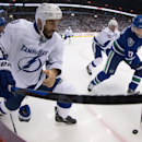 Tampa Bay Lightning's Jason Garrison, left, loses a glove, as Vancouver Canucks' Radim Vrbata, of the Czech Republic, moves the puck while being watched by Steven Stamkos (91) during the first period of an NHL hockey game Saturday, Oct. 18, 2014, in Vanco