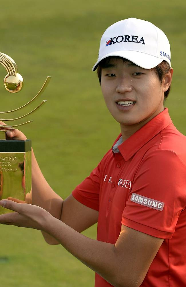 In this photo released by OneAsia, Lee Chang-woo of South Korea poses with the winner's trophy after the final round of the Asia-Pacific Amateur Championship at the Nanshan International Golf Club in Longkou, Shandong Province, China, Sunday, Oct. 27, 2013