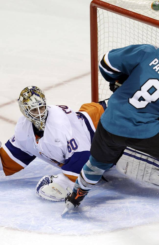 New York Islanders goalie Kevin Poulin (60) stops a shot from San Jose Sharks' Joe Pavelski (8) during the shootout of an NHL hockey game on Tuesday, Dec. 10, 2013, in San Jose, Calif. New York won 3-2