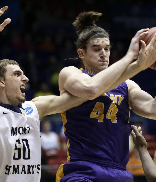 Albany center John Puk (44) pulls a rebound away from Mount St. Mary's center Taylor Danaher (50) in the first half of a first-round game of the NCAA college basketball tournament, Tuesday, March 18, 2014, in Dayton, Ohio