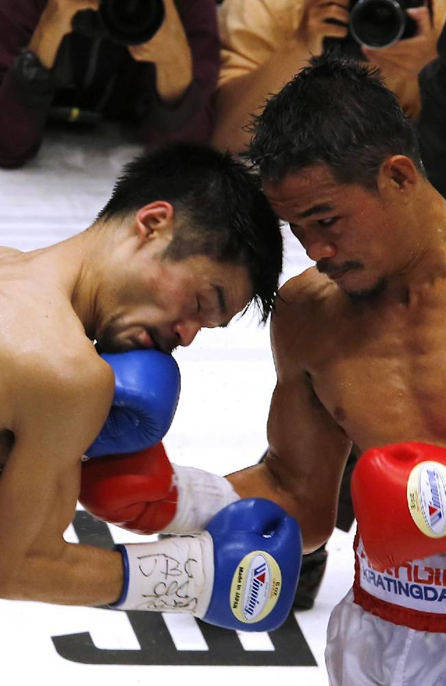 Thailand's Denkaosen Kaovichit, right, sends a right to Japan's Kohei Kono in the third round of their boxing match for the vacant WBA World super flyweight title in Tokyo, Wednesday, March 26, 2014. Kono knocked out Denkaosen in the eighth round to clinch the title
