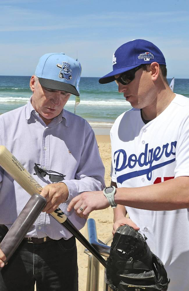 Former Australian cricket captain Allan Border, left, checks a bat with Los Angeles Dodgers catcher A.J. Ellis on Manly Beach in Sydney Wednesday, Nov. 20, 2013. The Dodgers and the Arizona Diamondbacks will play in their two-game series in Australia that opens next year's Major League Baseball season