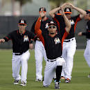 Miami Marlins' Giancarlo Stanton, front, leads a group of teammates including Christian Yelich, left, and Casey McGehee, right, in stretching at the start of spring training baseball practice Thursday, Feb. 20, 2014, in Jupiter, Fla. Friday was the first