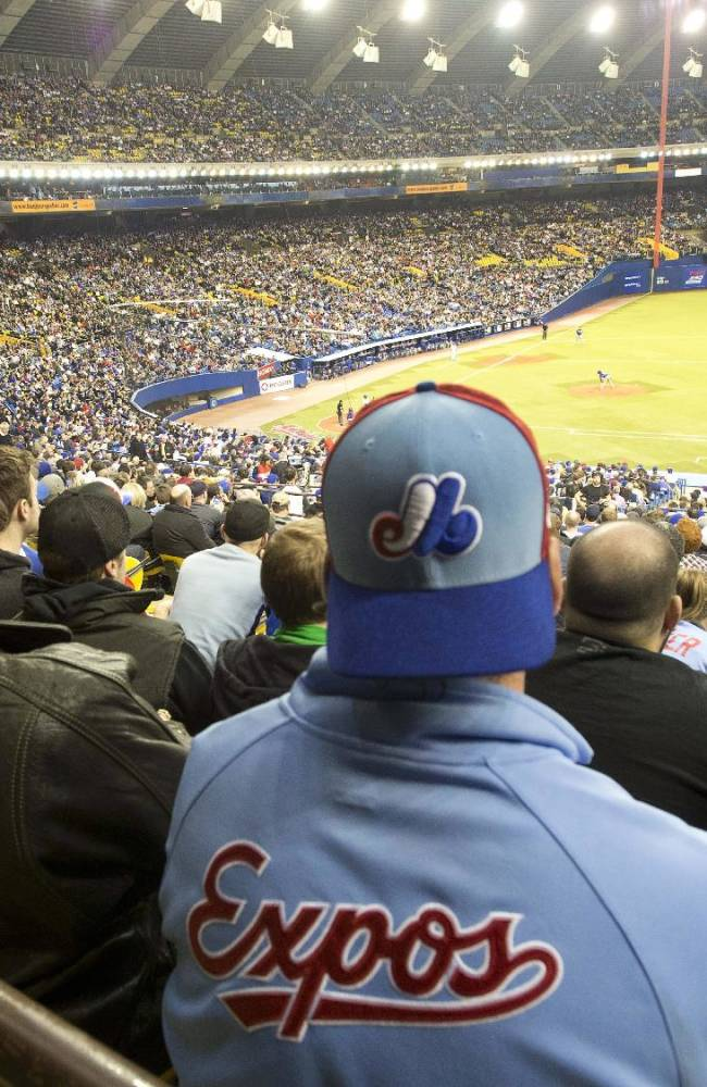Fans wear Montreal Expos uniforms as they watch the Toronto Blue Jays in a pre-season baseball game against the New York Mets Friday, March 28, 2014 in Montreal