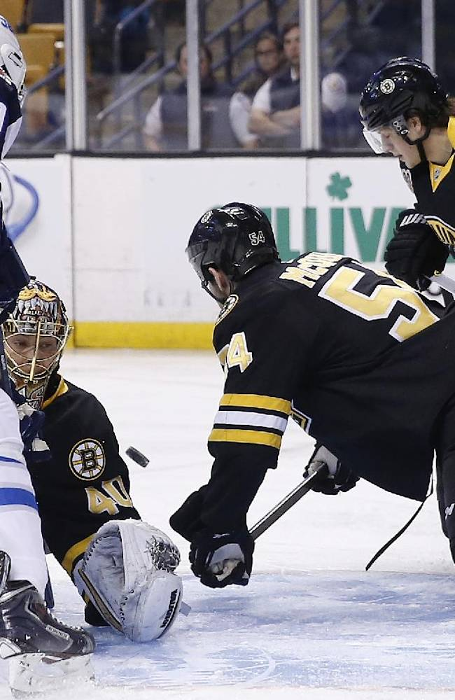 Winnipeg Jets' Evander Kane (9) looks for the rebound as the puck deflects of Boston Bruins' Tuukka Rask (40) as the Bruins' Adam McQuaid (54) and Torey Krug (47) defend in the first period of an NHL hockey game in Boston, Saturday, Jan. 4, 2014