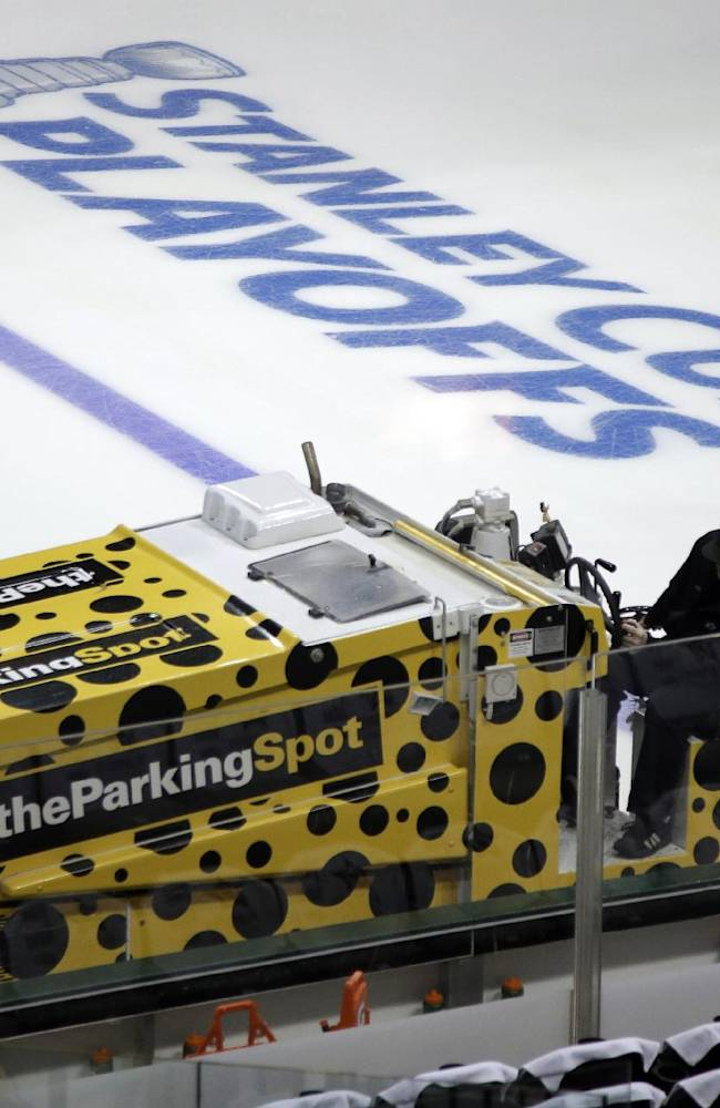 A member of the ice crew works the ice rink before a first-round NHL hockey Stanley Cup playoff series game between the Anaheim Ducks and Dallas Stars, Monday, April 21, 2014, in Dallas