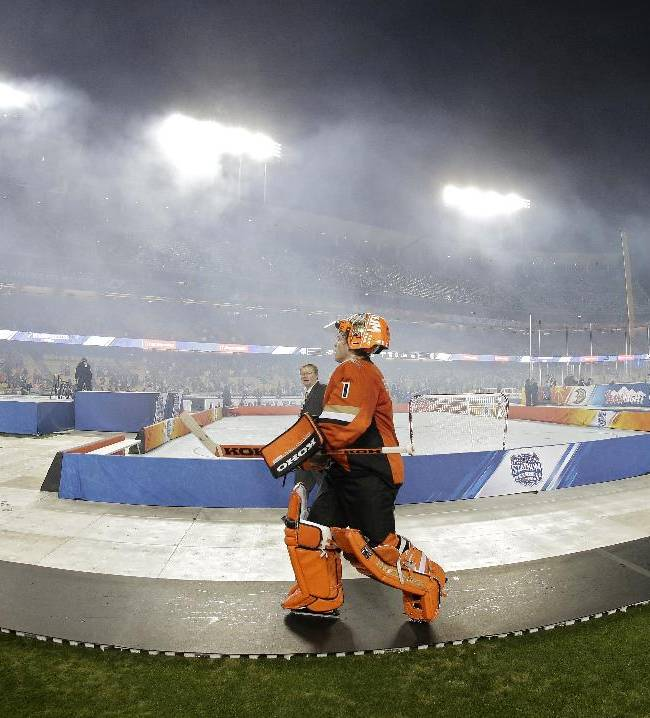 Anaheim Ducks goalie Jonas Hiller, of Switzerland, walks off the field after an NHL outdoor hockey game against the Los Angeles Kings at Dodger Stadium in Los Angeles, Saturday, Jan. 25, 2014