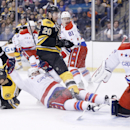 Boston Bruins' Gregory Campbell (11) falls after scoring on Washington Capitals' Braden Holtby, right, in the second period of an NHL hockey game in Boston, Saturday, March 1, 2014 The Associated Press