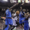 Sacramento Kings center DeMarcus Cousins, center, drives to the basket between Dallas Mavericks' Samuel Dalembert, left; Vince Evans, second from right; and Shawn Marion, right, during the fourth quarter of an NBA basketball game, Sunday, April 6, 2014, i