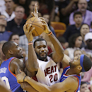 Miami Heat center Greg Oden (20) looks for an opening past Philadelphia 76ers forward Jarvis Varnado, left, and forward Brandon Davies, right, during the second half of an NBA basketball game on Wednesday, April 16, 2014, in Miami. The 76ers defeated the