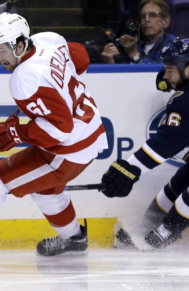 Detroit Red Wings' Xavier Ouellet, left, of France, and St. Louis Blues' Roman Polak, of the Czech Republic, chase after a loose puck during the second period of an NHL hockey game Sunday, April 13, 2014, in St. Louis