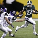 Michigan State running back Le'Veon Bell, right, stiff-arms TCU linebacker Joel Hasley, center, as TCU cornerback Jason Verrett, left, pursues during the first half of the Buffalo Wild Wings Bowl NCAA college football game Saturday, Dec. 29, 2012, in Tempe, Ariz. (AP Photo/Paul Connors)