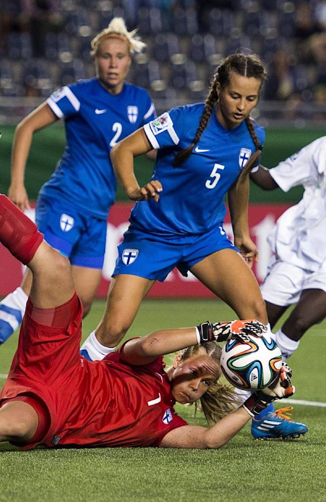 Finland's keeper Vera Varis makes a save as teammates Tia Halinen, left, and Katarina Naumanen, center, defend against Ghana's Veronica Appiah at the FIFA U20 Women's World Cup in Moncton, New Brunswick, on Tuesday, Aug. 12, 2014. Ghana won 2-1