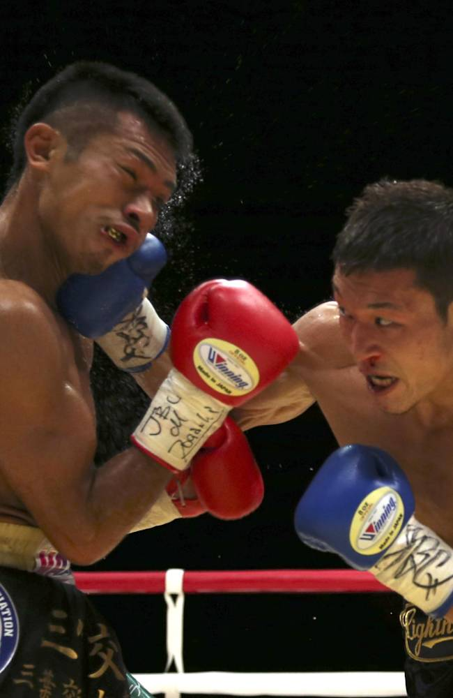 Japanese champion Takashi Uchiyama, left, gets a right from compatriot challenger Daiki Kaneko in the fourth round of their WBA super featherweight boxing title bout in Tokyo, Tuesday, Dec. 31, 2013. Uchiyama defended his title by a unanimous decision