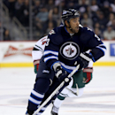 Winnipeg Jets Dustin Byfuglien (33) carries the puck into the Minnesota Wild's zone during second period pre-season NHL hockey action in Winnipeg, Monday, Sept. 22, 2014 The Associated Press