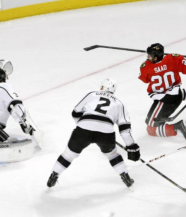 Chicago Blackhawks left wing Brandon Saad (20) scores past Los Angeles Kings goalie Martin Jones (31) as Matt Greene (2), Mike Richards (10) and Bryan Bickell (29) are near during the first period of an NHL hockey game Monday, Dec. 30, 2013, in Chicago
