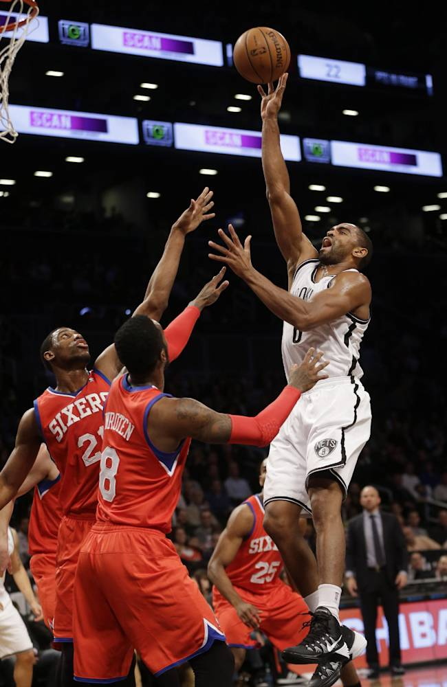 Brooklyn Nets' Alan Anderson, right, sinks a basket and draws a foul while Philadelphia 76ers' Thaddeus Young, left, and Tony Wroten (8) defend during the first half of the NBA basketball game at the Barclays Center, Monday, Dec. 16, 2013, in New York
