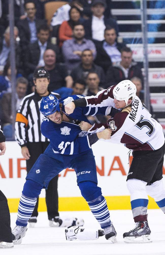 Toronto Maple Leafs forward Troy Bodie, center left, fights against Colorado Avalanche forward Cody McLeod during the second period of an NHL hockey game in Toronto on Tuesday, Oct. 8, 2013