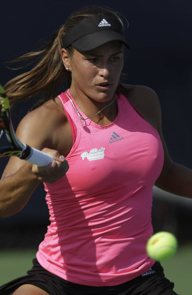 Monica Puig, of Puerto Rico, returns a shot against Andrea Petkovic, of Germany, during the second round of the 2014 U.S. Open tennis tournament, Wednesday, Aug. 27, 2014, in New York