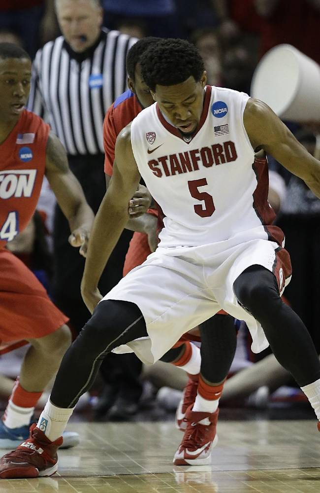 Stanford guard Chasson Randle (5) vies for a loose ball as Stanford forward Josh Huestis (24) looks on during the first half in a regional semifinal game at the NCAA college basketball tournament, Thursday, March 27, 2014, in Memphis, Tenn