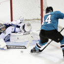 Winnipeg Jets goalie Ondrej Pavelec, left, of the Czech Republic, stops a shot from San Jose Sharks defenseman Marc-Edouard Vlasic during the first period of an NHL hockey game Saturday, Oct. 11, 2014, in San Jose, Calif The Associated Press