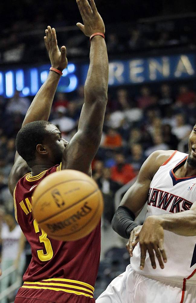 Atlanta Hawks' Paul Millsap, right, passes the ball behind the back of Cleveland Cavaliers' Dion Waiters in the first quarter of an NBA basketball game, Friday, April 4, 2014, in Atlanta