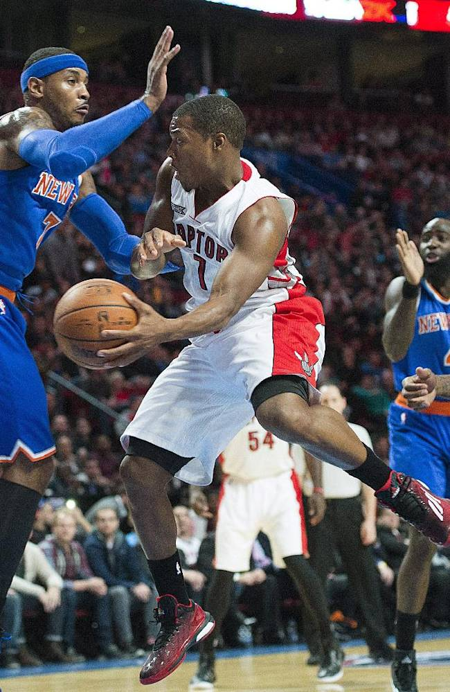 Toronto Raptors' Kyle Lowry, center, makes a pass as New York Knicks' Carmelo Anthony, left, and Amare Stoudemire, right, defend during first-quarter NBA preseason basketball game action in Montreal, Friday, Oct. 24, 2014