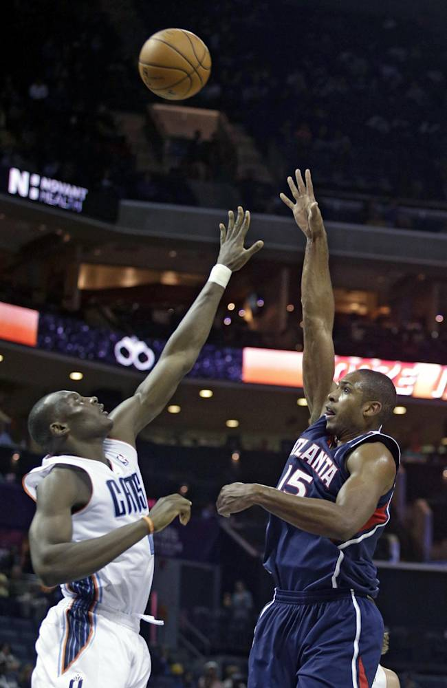 Atlanta Hawks forward Al Horford shoots over Charlotte Bobcats forward Bismack Biyombo, of the Democratic Republic of Congo, in the second half of an NBA basketball game in Charlotte, N.C., Monday, Nov. 11, 2013. Atlanta won 103-94